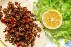 Roasted minced beef with chili pepper on tortilla with lettuce and lemon Royalty Free Stock Photos