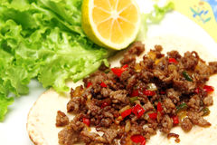 Roasted minced beef with chili pepper on tortilla with lettuce and lemon Royalty Free Stock Images