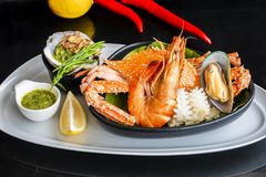 Roasted Mixed Seafood Contain Blue Crabs, Mussels, Big Shrimps, Calamari Squids with Spicy Chili Sauce and Lemon on Dish, on black stock photo