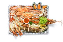 Roasted Mixed Seafood Platter Set contain Lobster, Fish, Blue Clab, Big Prawns, Mussels Clams and Calamari Squids with pieces of. Lemon & vegetables, Isolated royalty free stock photo