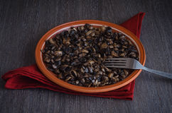 Roasted mushrooms on plate, wooden background Stock Photo