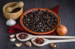 Roasted mushrooms with spices on plate, wooden background Royalty Free Stock Images