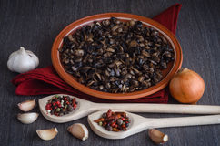 Roasted mushrooms with spices on plate, wooden background Royalty Free Stock Image