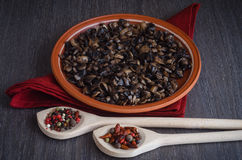 Roasted mushrooms with spices on plate, wooden background Royalty Free Stock Photos
