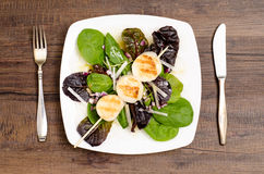 Roasted mussels on a leaf salad. With fork and knife Royalty Free Stock Photography