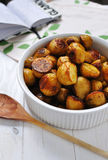 Roasted new potatoes. In white ramekin with wooden spoon Royalty Free Stock Photo