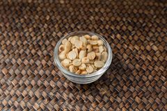 Roasted nuts in clear glass cup on the tray. Roasted nuts in clear glass cup on the tray, Natural light beautiful Royalty Free Stock Image