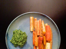 Roasted organic heirloom carrots with carrot top pesto stock images