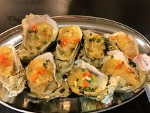Grilled oyster seafood Chinese cuisine food. Roasted oysters with spices in restaurant in China Asia. Grilled fresh seafood. Exotic traditional Chinese cuisine Stock Image