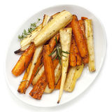 Roasted Parsnips and Carrots Overhead View. Roasted parsnips and carrots garnished with rosemary and thyme.  White plate, overhead view Stock Photo