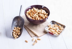 Roasted peanuts on a bowl over white wooden background Stock Photos