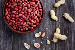 Roasted peanuts in bowl on wooden table Stock Photo