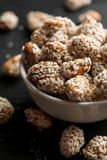 Roasted peanuts covered with sesame in white ceramic bowl, vertical.  royalty free stock image
