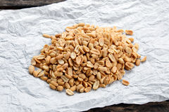 Roasted peanuts salted on crumpled paper and old wooden table. Royalty Free Stock Photo