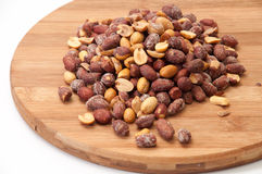 Roasted peanuts in the shell on a kitchen wooden board Royalty Free Stock Image