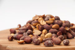 Roasted peanuts in the shell on a kitchen wooden board Royalty Free Stock Images