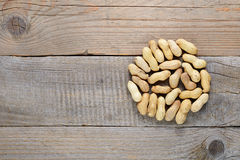 Roasted peanuts in shell on wooden table Stock Images