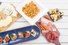Roasted peanuts and starters with ham and open sandwiches Stock Images