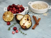 Roasted pears and lemon with cranberries, cinnamon and herbs royalty free stock images