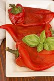 Roasted, peeled peppers with basil royalty free stock photography