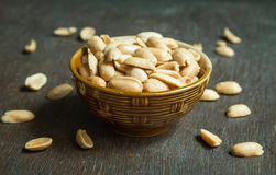 Roasted peeled salted peanuts in rustic bowl on wooden background Royalty Free Stock Photography