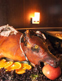 Roasted pig. Delicious roasted pig on the celebratory wedding decorated table with oranges, lettuce and apple Stock Photo
