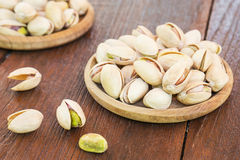 Roasted pistachio on wooden plate Stock Photo
