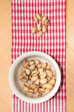 Roasted pistachios in a bowl on red tablecloth Royalty Free Stock Photography