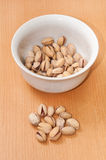 Roasted pistachios in a bowl on wooden table Stock Image