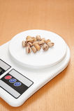 Roasted pistachios on a digital kitchen scale Stock Photos