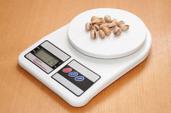 Roasted pistachios on a digital kitchen scale Stock Photo