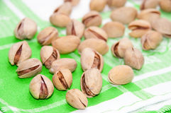 Roasted pistachios on a green tablecloth Royalty Free Stock Images