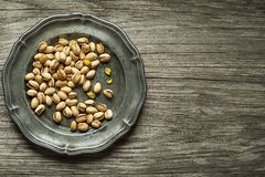 Roasted Pistachios nuts in plate. On wooden table background stock image