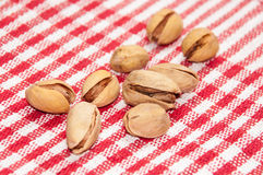 Roasted pistachios on a red tablecloth Royalty Free Stock Images