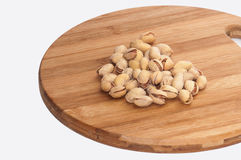 Roasted pistachios in the shell over the kitchen wooden board Royalty Free Stock Image