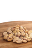 Roasted pistachios in the shell over the kitchen wooden board Royalty Free Stock Photos