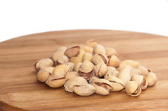 Roasted pistachios in the shell over the kitchen wooden board Stock Photo