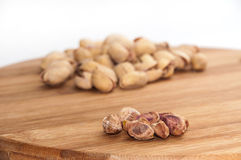 Roasted pistachios, shelled on a kitchen wooden board Royalty Free Stock Images