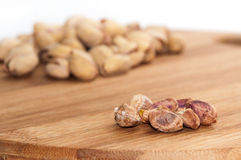 Roasted pistachios, shelled on a kitchen wooden board Royalty Free Stock Photos