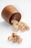 Roasted pistachios spilled from a wooden bowl over white backgro Royalty Free Stock Photography