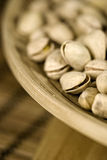 Roasted pistachios in wooden bowl. Placed on the table Stock Photos