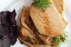 Roasted Pork. Slices of Ripe Roasted Pork with Greens on white plate top view stock photo
