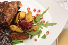 Roasted pork with cheese and baked potatoes with spices on plate stock photography