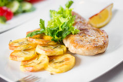Roasted pork chop with potatoes on dish Royalty Free Stock Photography