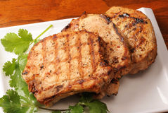 Roasted Pork Chops. Three roasted pork chops on a white plate stock images