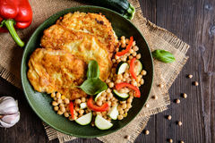 Roasted pork cutlets coated in cheese and breadcrumbs, served with chick peas and vegetable Royalty Free Stock Image