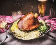Roasted pork knuckle eisbein with mashed potatoes and braised boiled cabbage in plate with cutlery  and beer on rustic table, fron Royalty Free Stock Photo