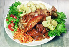 Roasted pork knuckle. In honey sauce and garnished with boiled potatoes, salad and carrots in vintage style royalty free stock image