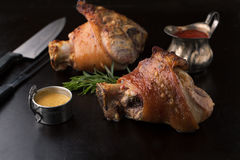 Roasted pork knuckle with mustard, spices and rosemary stock images