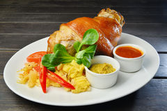 Roasted pork knuckle with sause. Roasted pork knuckle with potatoes sause and vegetables Stock Images